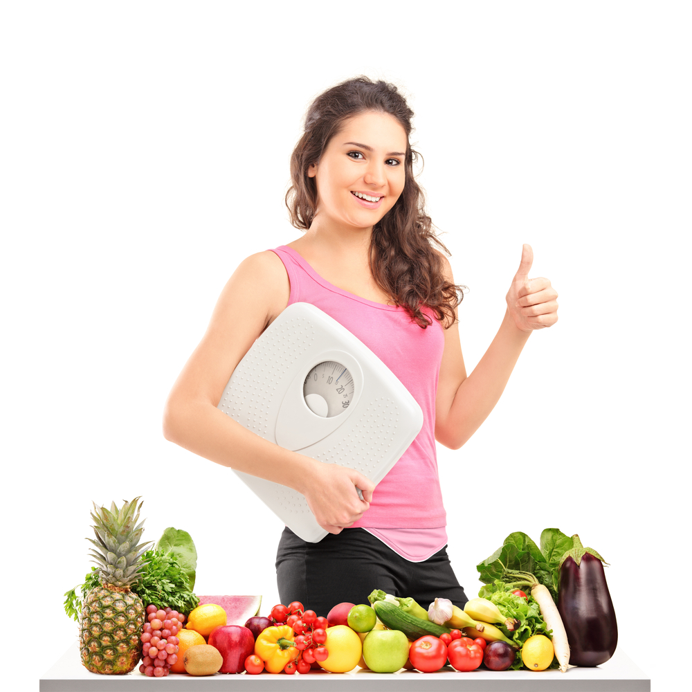 Diet Health: Young Female Holding A Weight Scale And Giving A Thumb Up